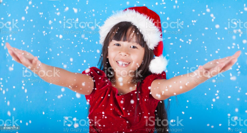 Cute little Asian girl catching snow flakes stock photo