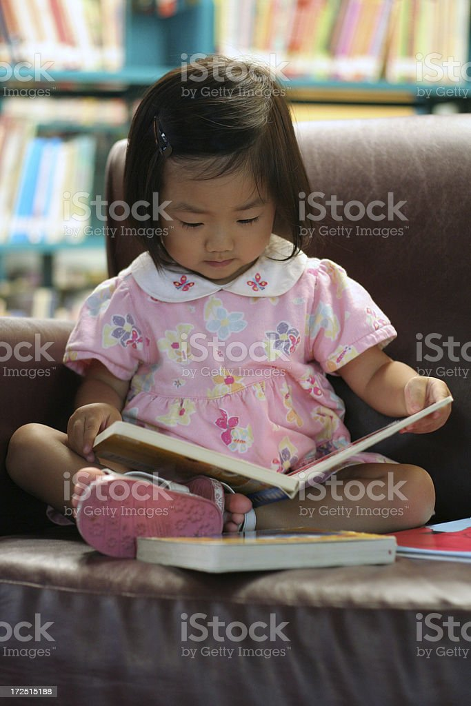 Cute little Asian girl reading a book in preschool library royalty-free stock photo