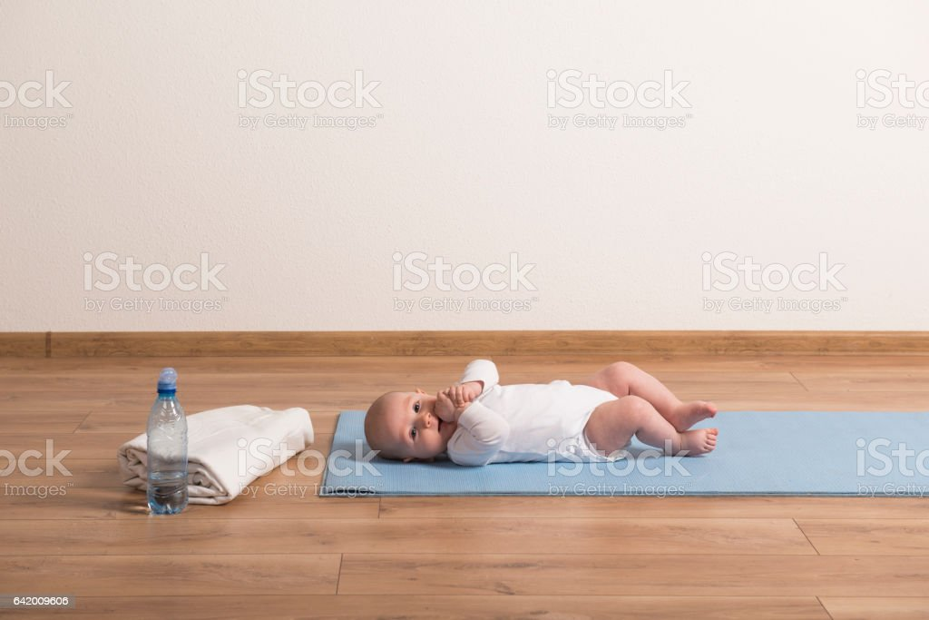 Cute little baby boy lying on exercise mat, sucking thumb stock photo