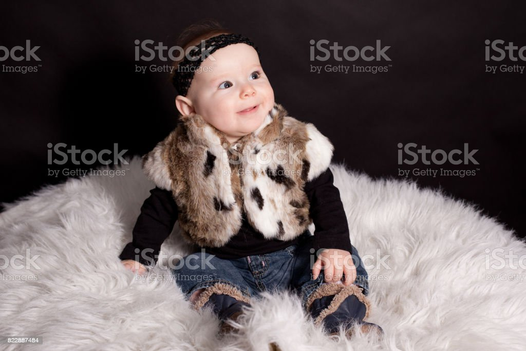Cute little baby in fur coat stock photo