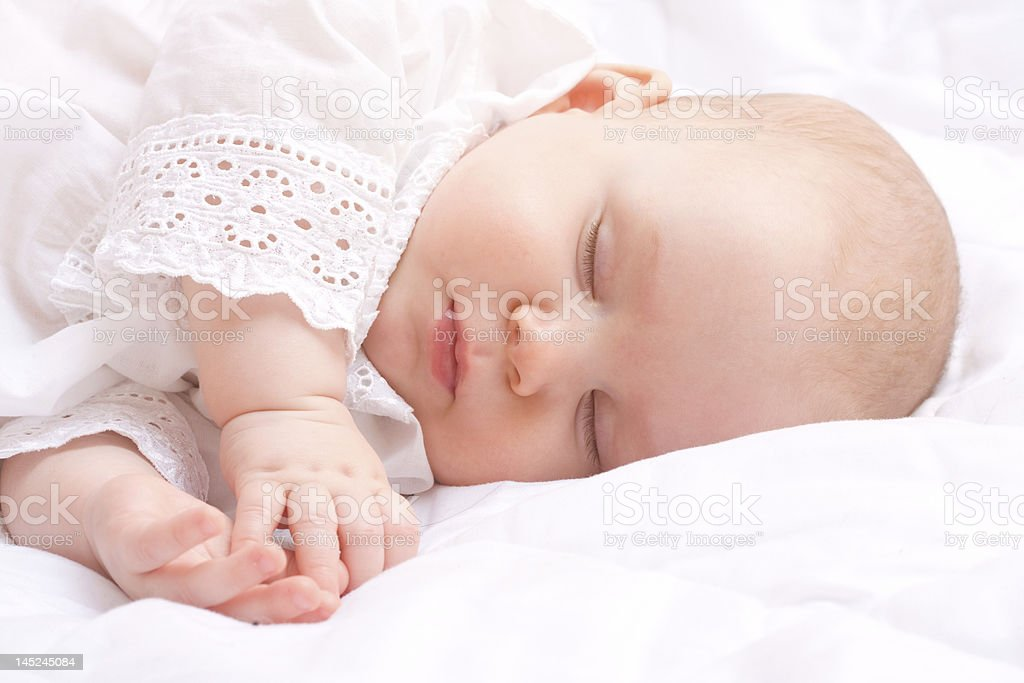 Cute little baby peacefully sleeping with hands together royalty-free stock photo