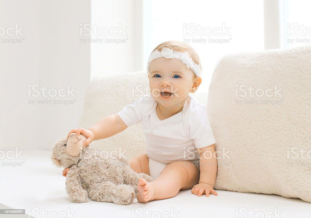 Cute little baby playing with toy home in white room stock photo