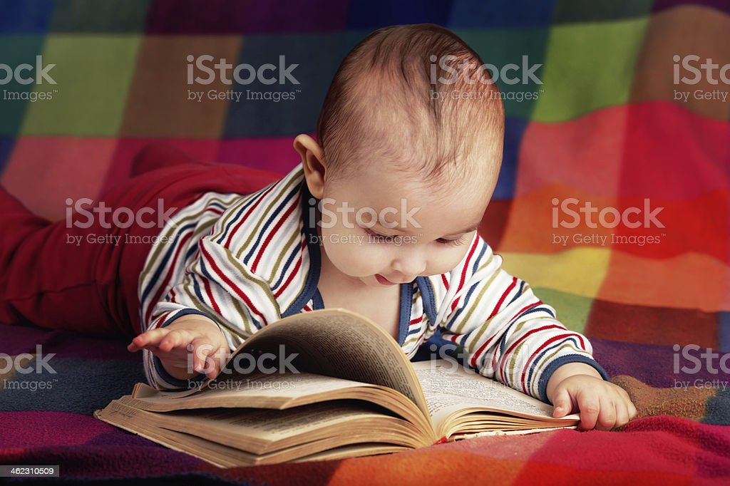 cute little baby reading book stock photo