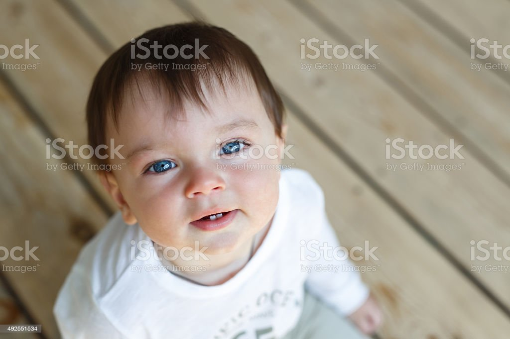 Cute little baby sitting on a wooden floor stock photo