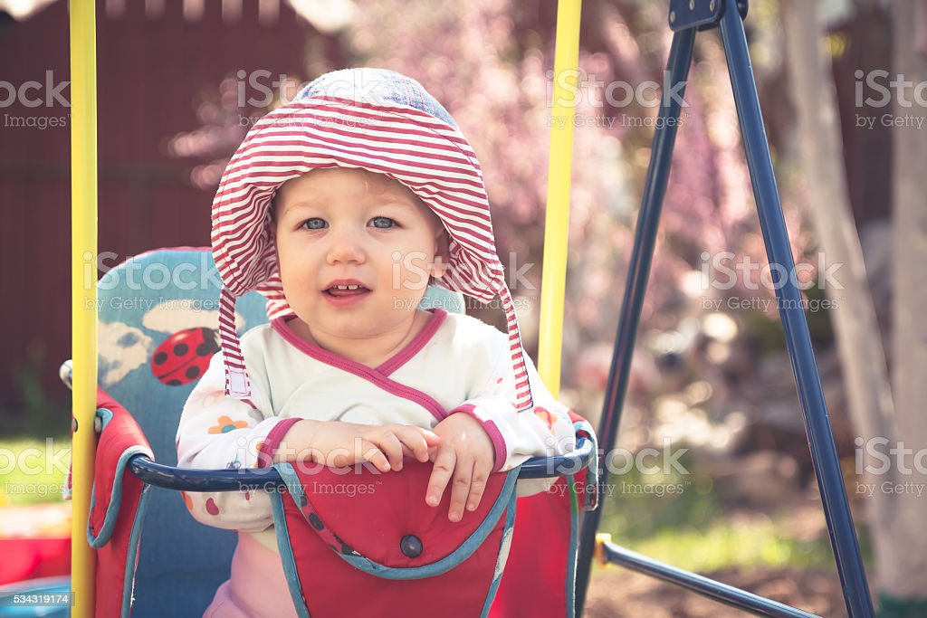 Cute little baby sitting on swings in sunny summer day stock photo