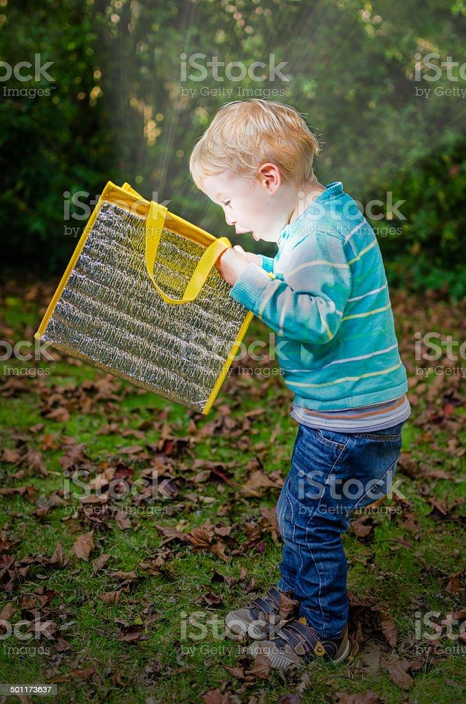 Cute little blond boy looking inside bag with glow light stock photo