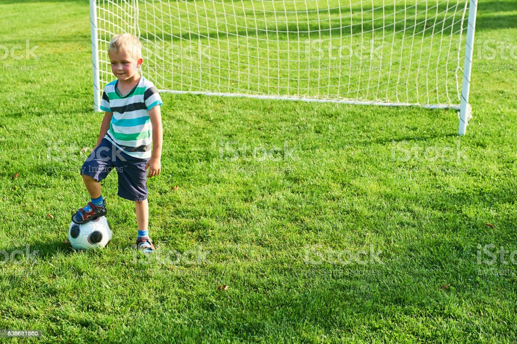 Cute little blond boy playing at being a goalkeeper stock photo