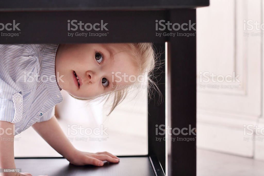 Cute little blond girl climbed in recess table stock photo