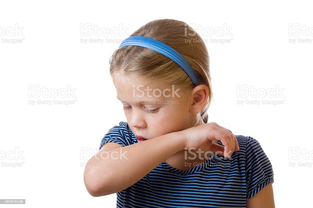 Cute little blond girl coughing in her elbow on white stock photo