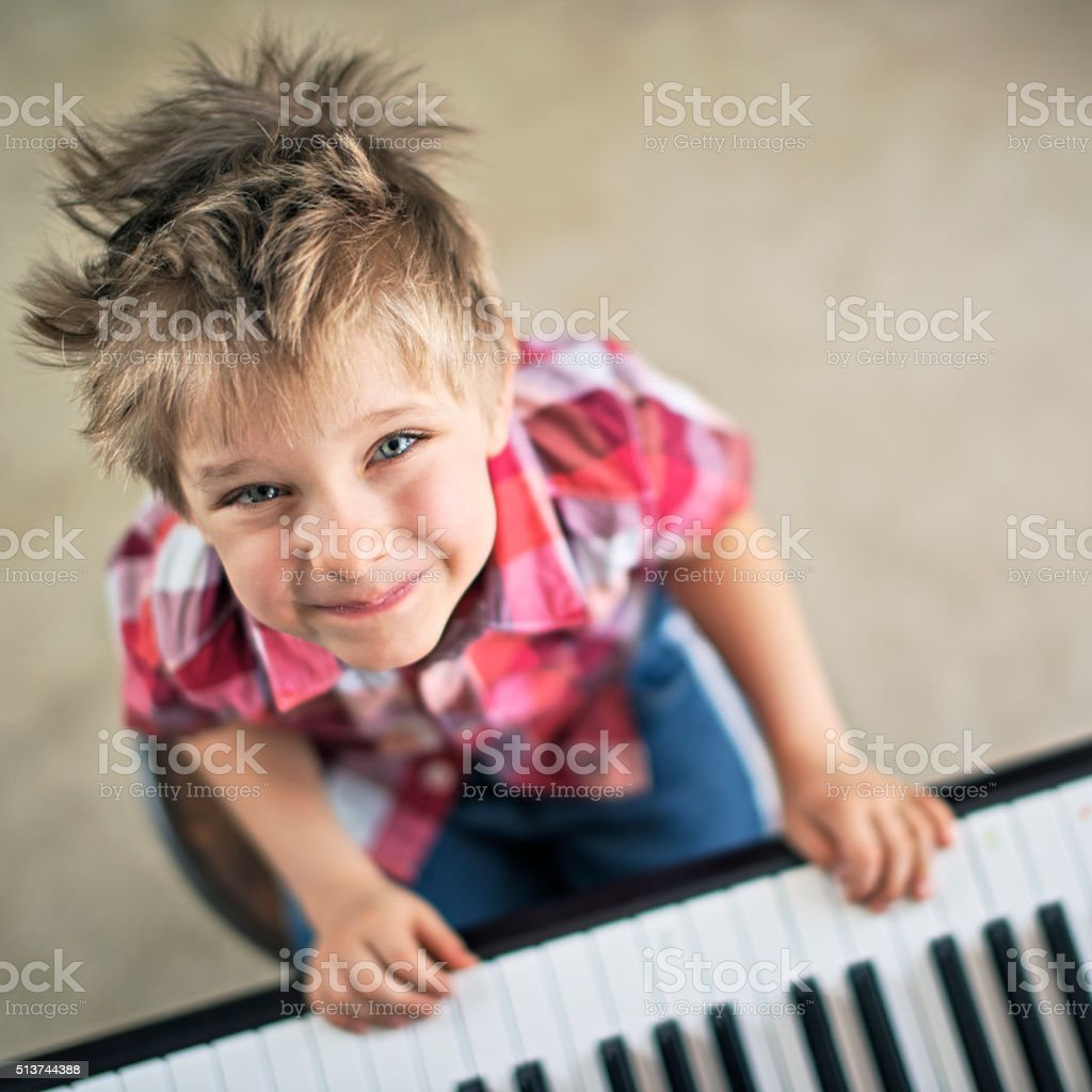 Cute little boy aged 4 playing piano stock photo