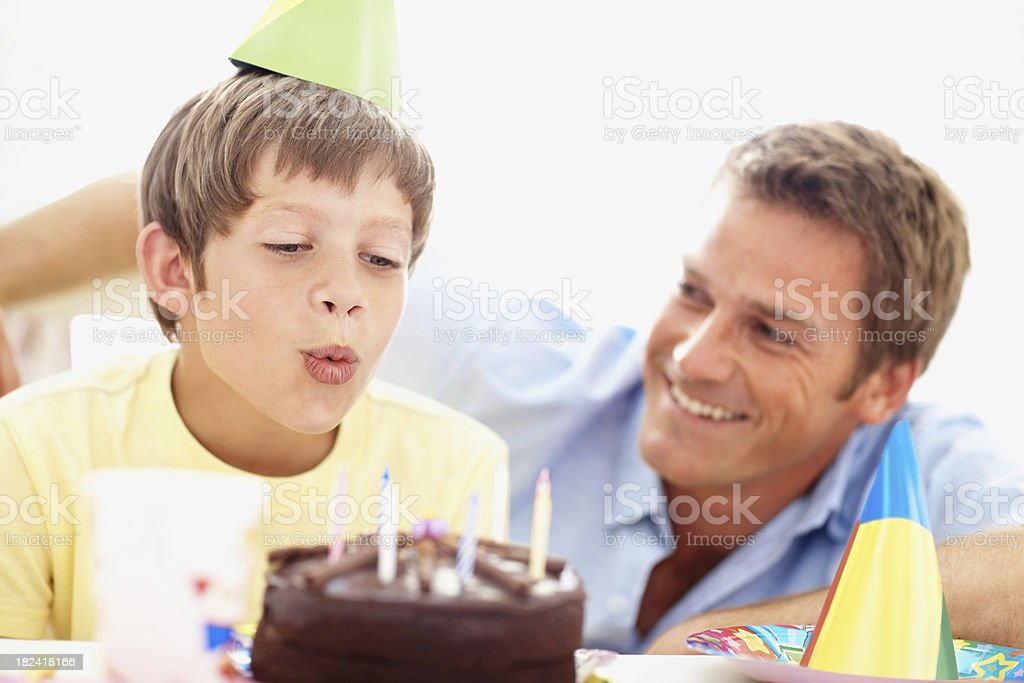 Cute little boy blowing off the birthday candles royalty-free stock photo