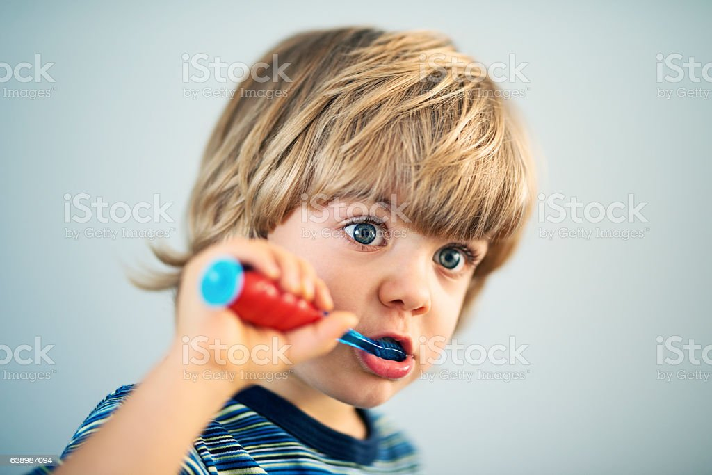 Cute little boy brushing teeth stock photo