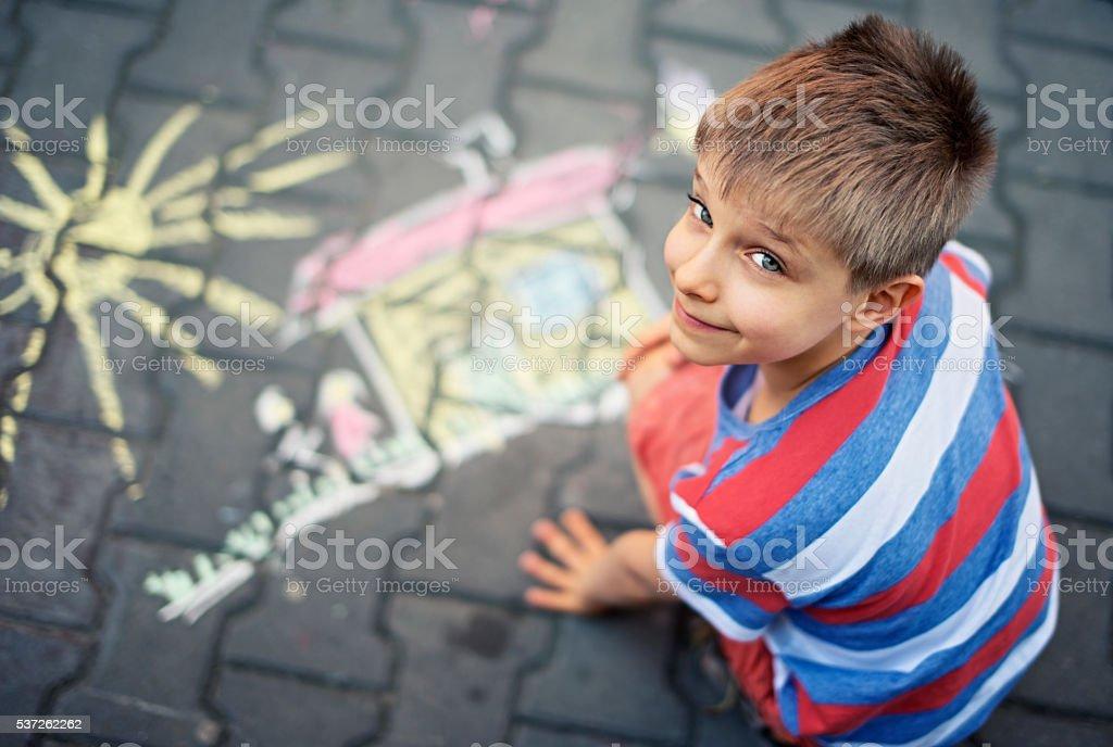Cute little boy chalking on street stock photo