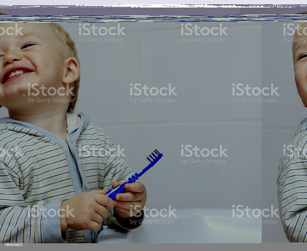 Cute little boy cleans his teeth in bathroom royalty-free stock photo