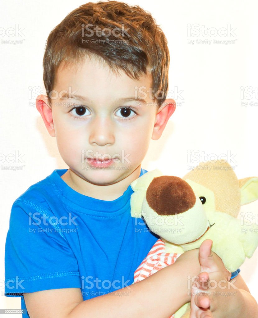 Cute little boy cuddling his favourite stuffed toy stock photo