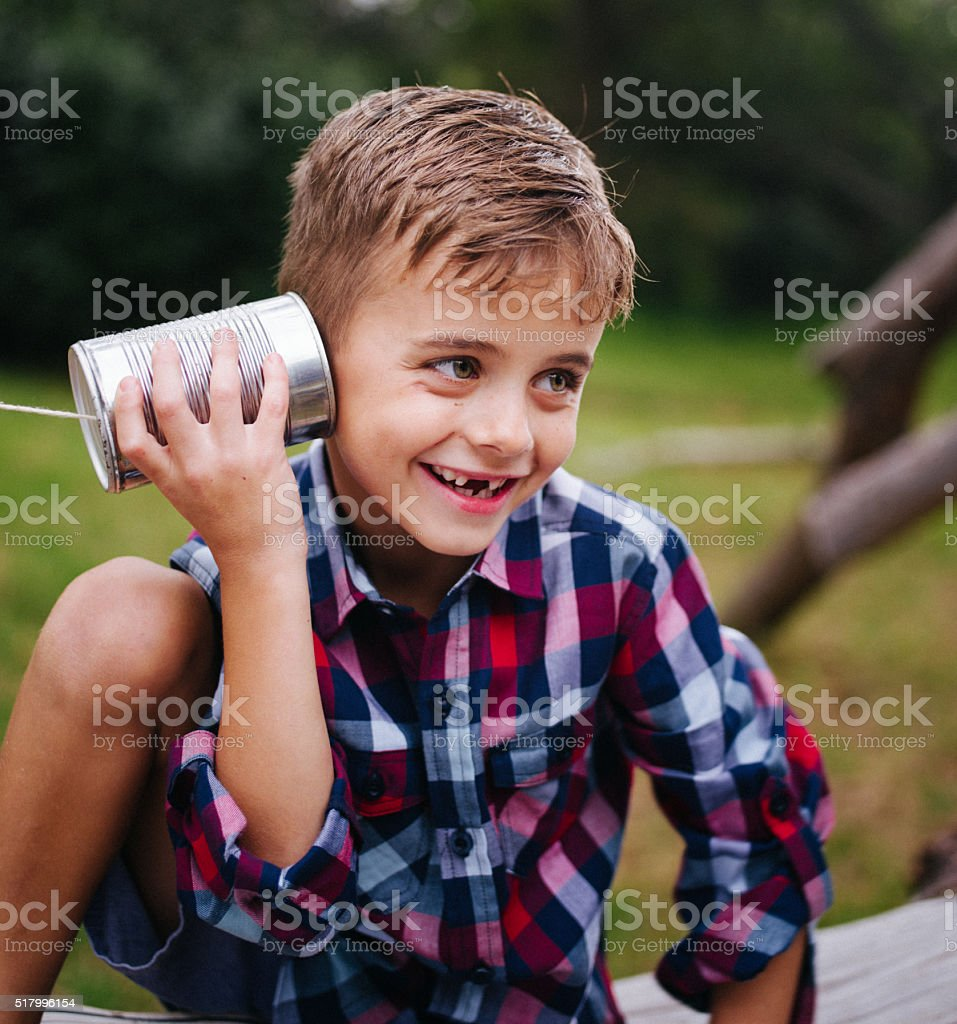 Cute little Boy curiously listening tin can phone in park stock photo
