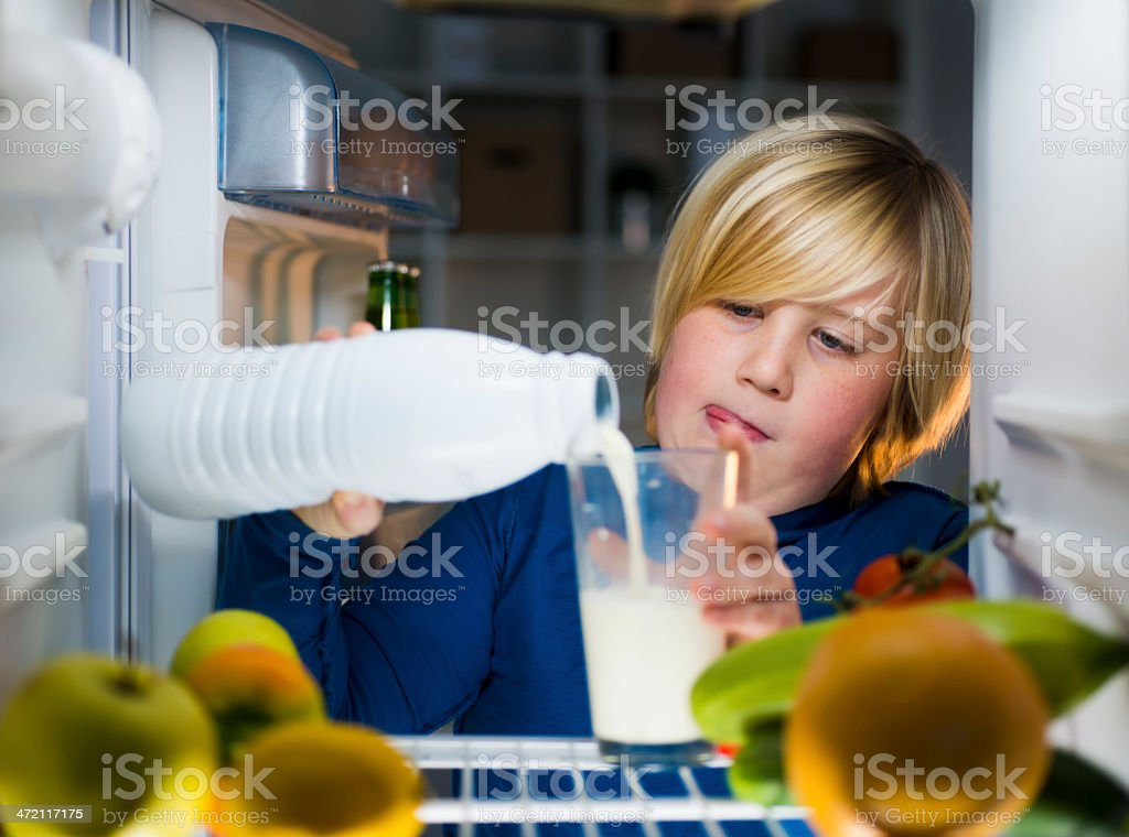 Cute little boy drink milk in fridge at the night stock photo