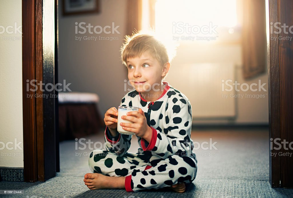 Cute little boy drinking glass of milk in morning stock photo