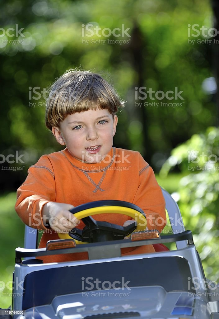 cute little boy driving  an electric car stock photo