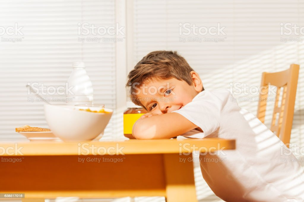 Cute little boy during breakfast in the kitchen stock photo
