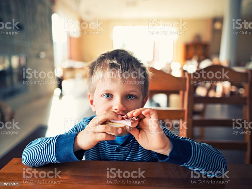 Cute little boy eating breakfast stock photo