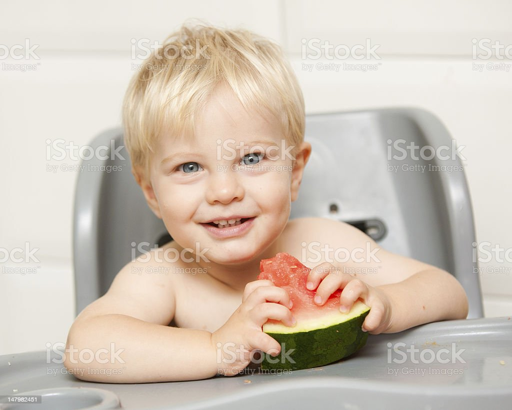 Cute little boy eats watermelon in his high chair royalty-free stock photo