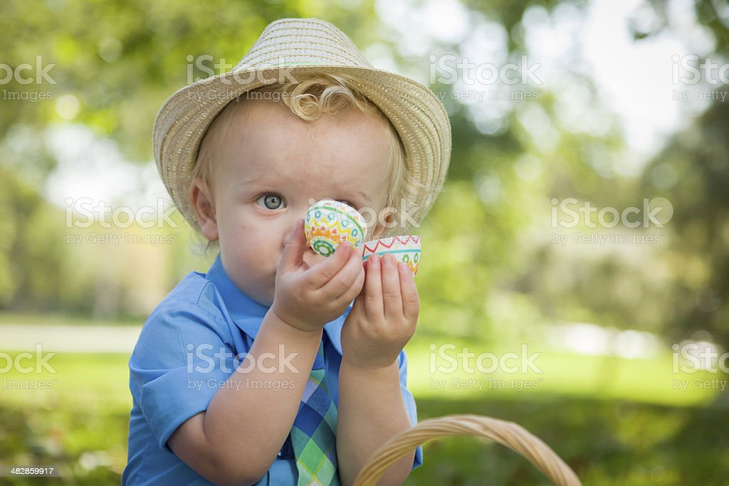 Cute Little Boy Enjoying His Easter Eggs Outside in Park stock photo