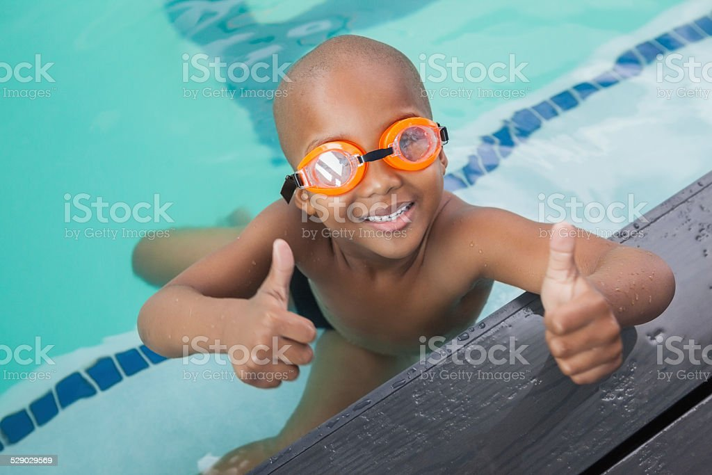 Cute little boy giving thumbs up at the pool stock photo