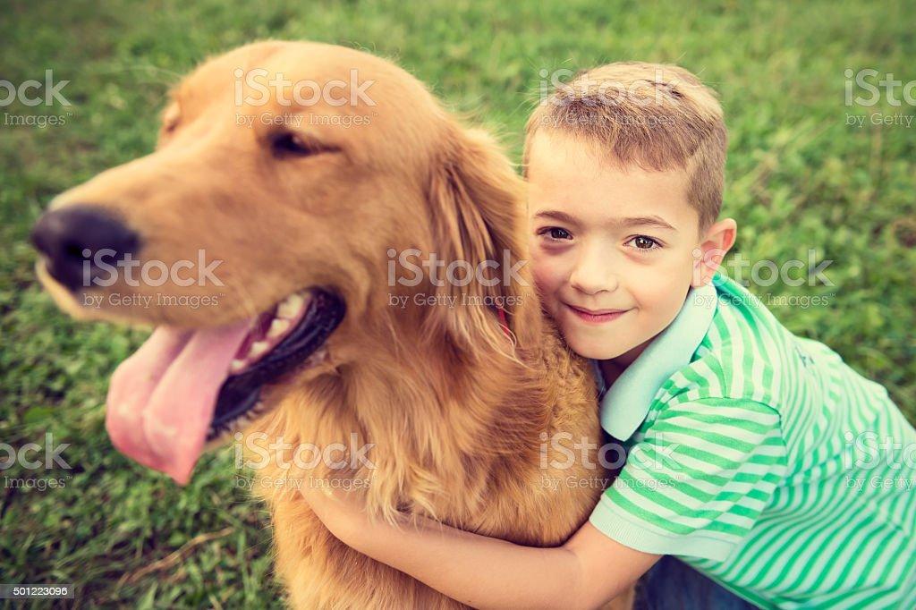 Cute little boy hugging his golden retriever pet dog stock photo