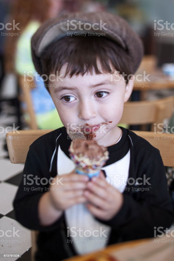 Cute little boy in a brown newsboy gatsby drivng cap and tuxedo t-shirt eating a messy chocolate ice cream cone stock photo