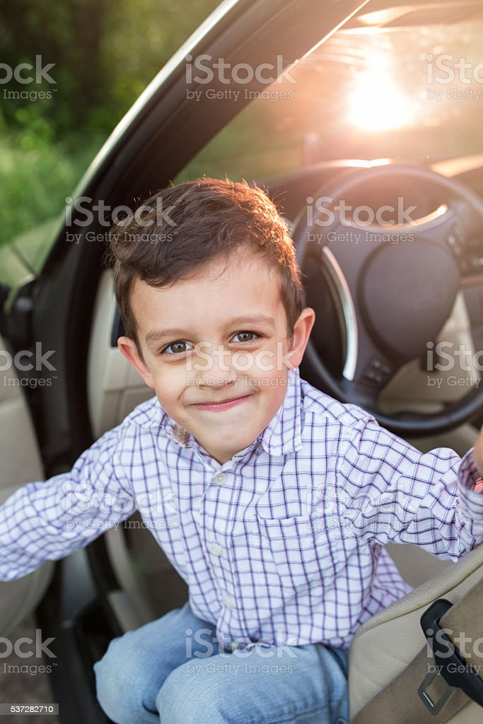 Cute little boy in a car smiling towards the camera. stock photo