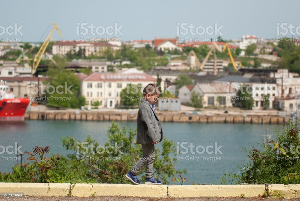 cute little boy in jacket walking on the curb in the background of the sea port stock photo