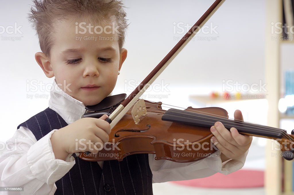 Cute little boy is practicing the violin stock photo