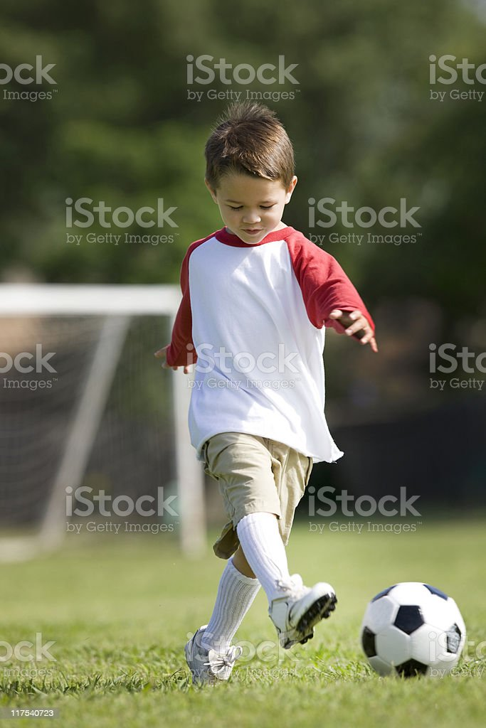 Cute Little Boy Kicking A Soccer Ball royalty-free stock photo