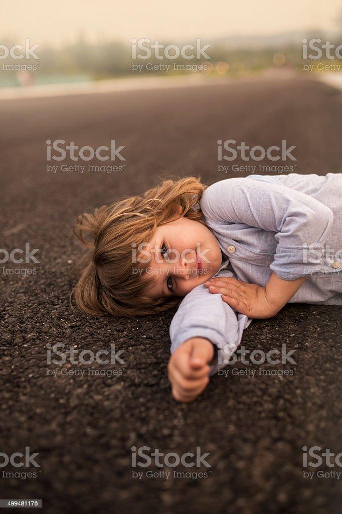 Cute little boy lying on road. stock photo