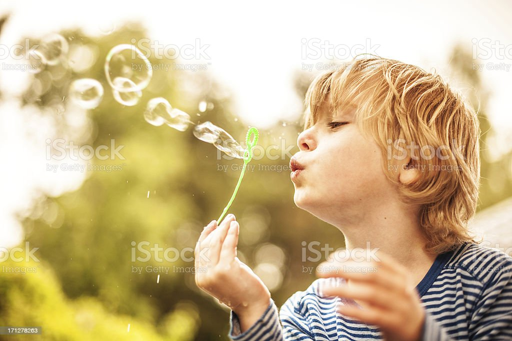 Cute little boy outdoors blowing bubbles stock photo