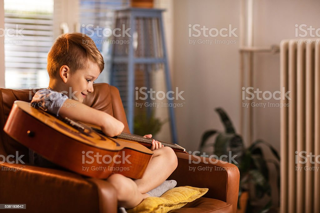 Cute little boy playing acoustic guitar at home. stock photo