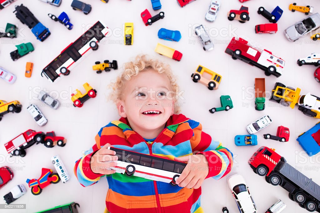 Cute little boy playing with toy cars stock photo