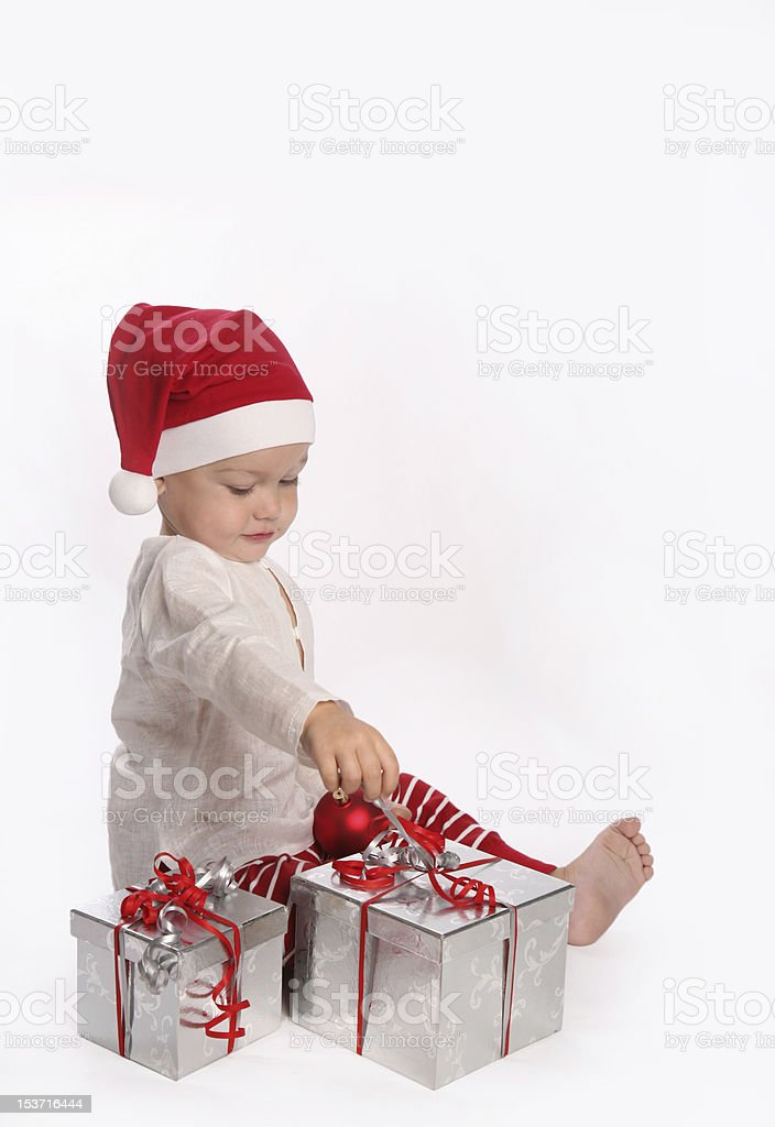 Cute little boy playing with two Christmas gifts opening royalty-free stock photo