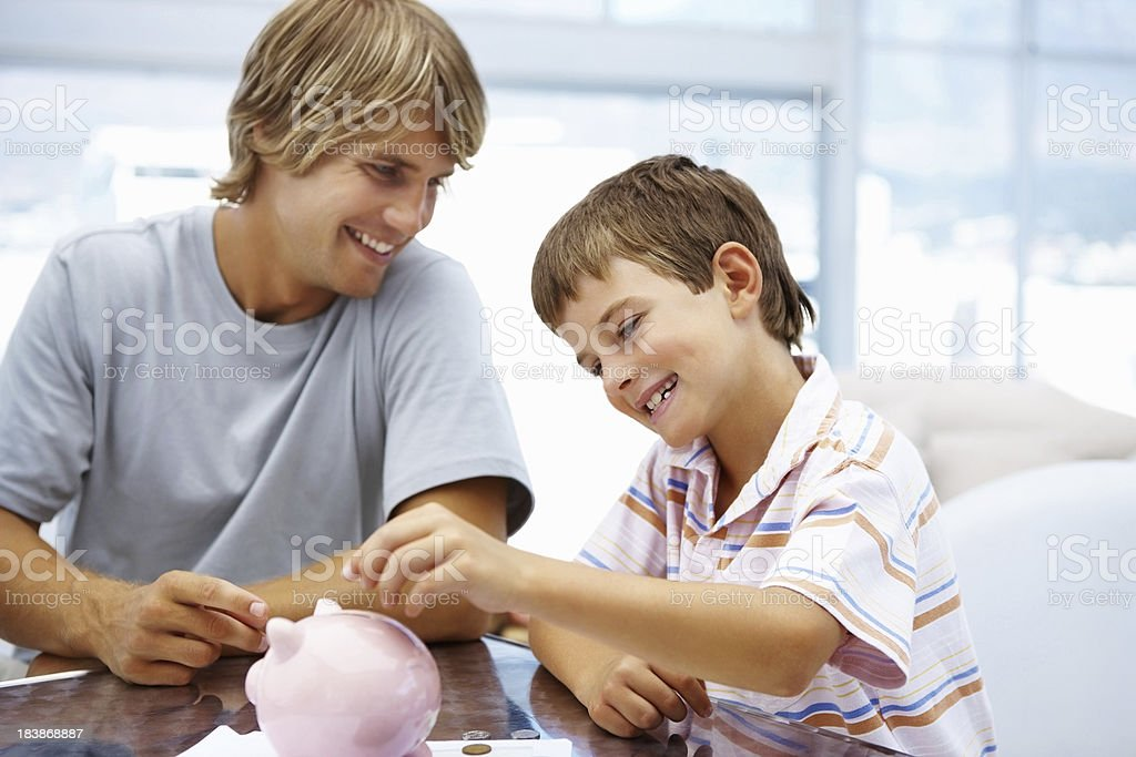 Cute little boy putting money in piggy bank royalty-free stock photo
