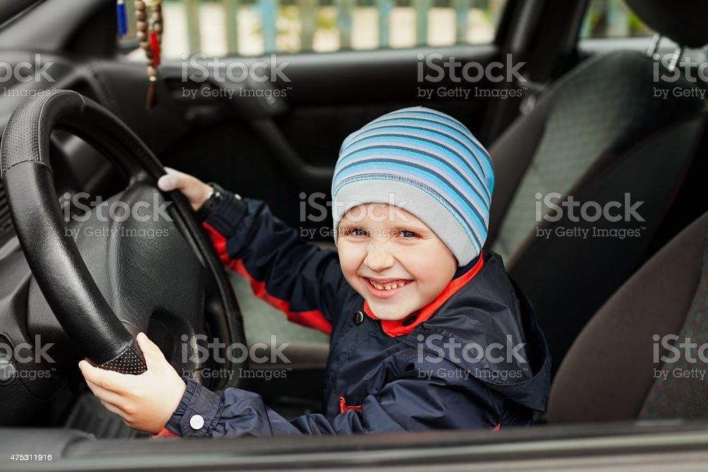 cute little boy sitting behind the steering wheel of car stock photo