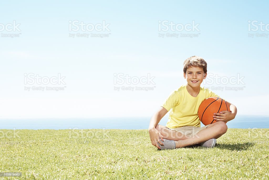 Cute little boy sitting on grass with a basketball - Copyspace stock photo