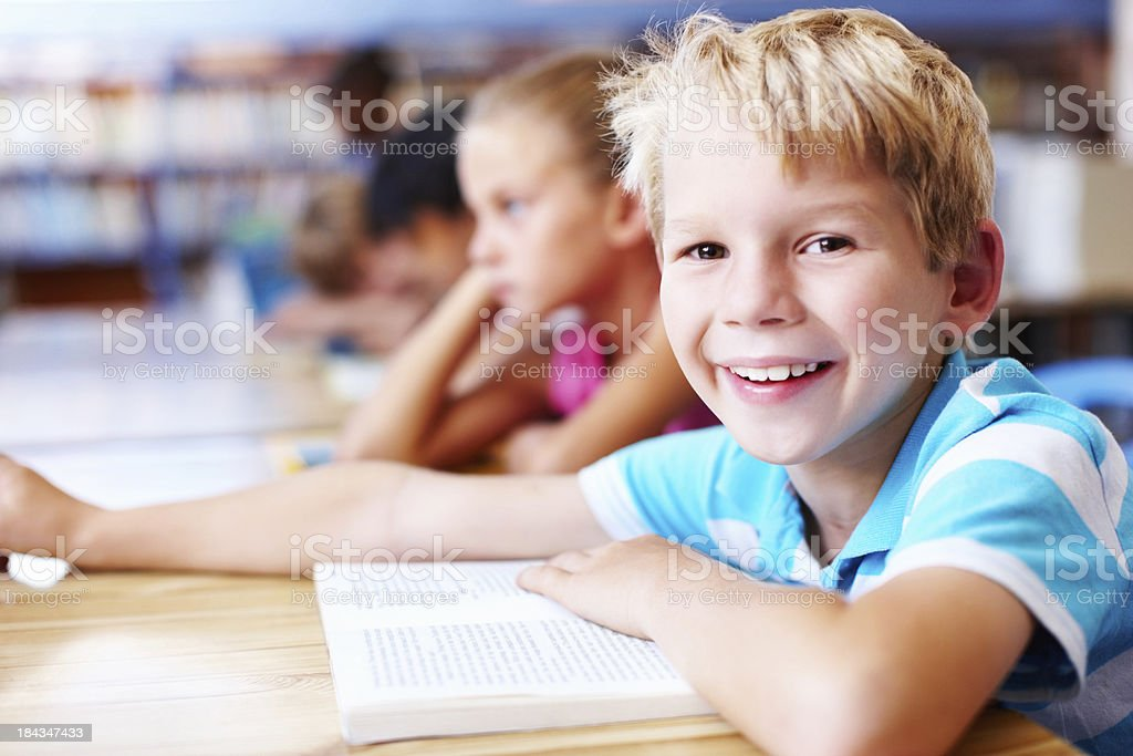 Cute, little boy smiling with friends in the library royalty-free stock photo