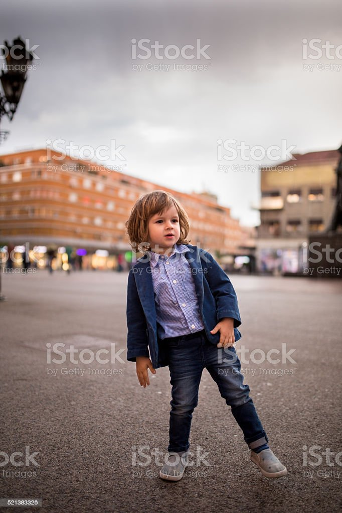 Cute little boy spending a day in the city. stock photo