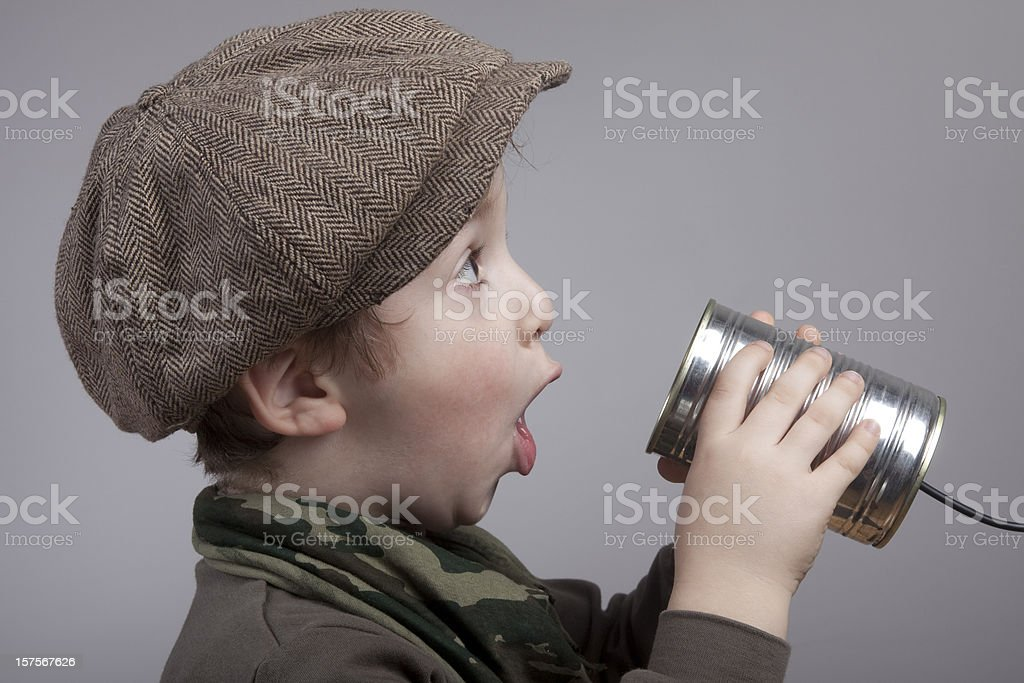 Cute Little Boy Surprised While Communicating On Tin Can Phone stock photo