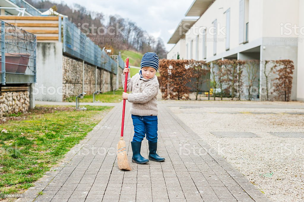 Cute little boy sweeping the backyard stock photo