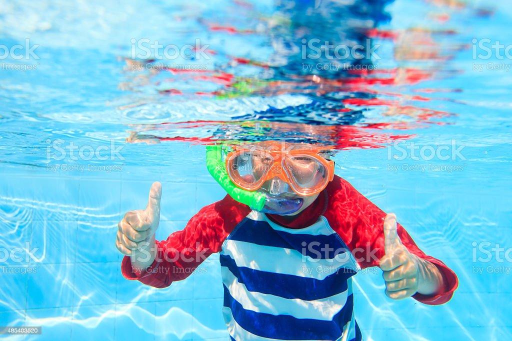 cute little boy swimming underwater stock photo