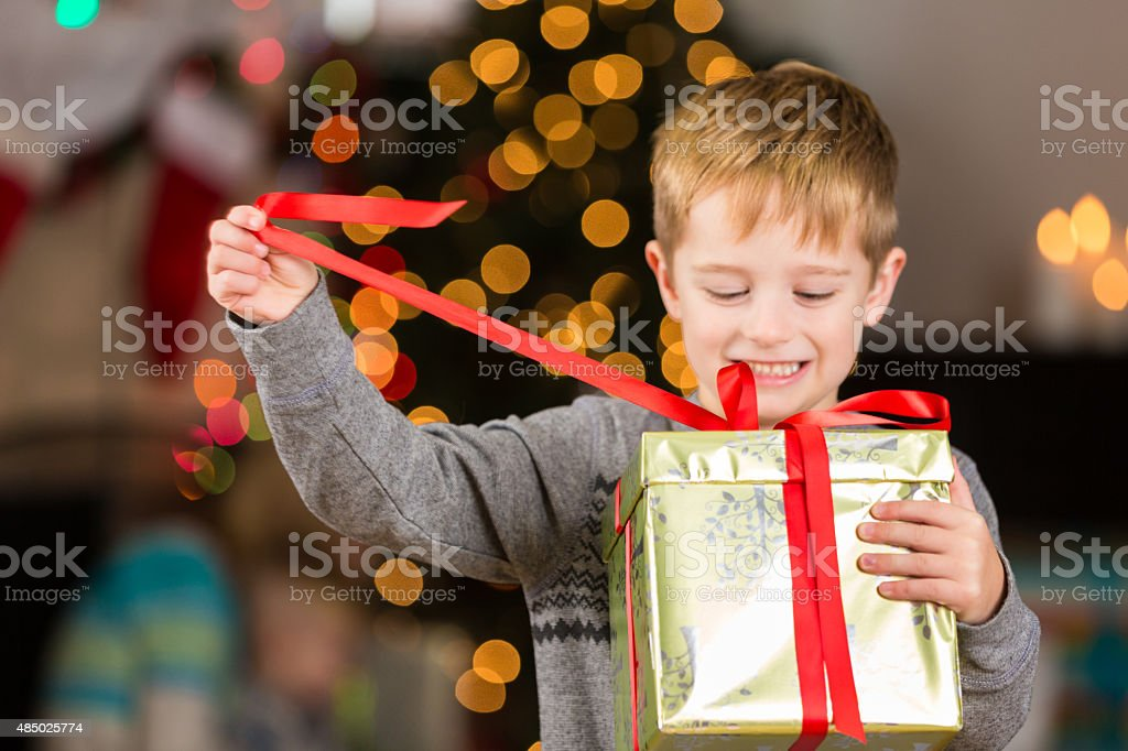 Cute little boy unwrapping Christmas present excitedly stock photo