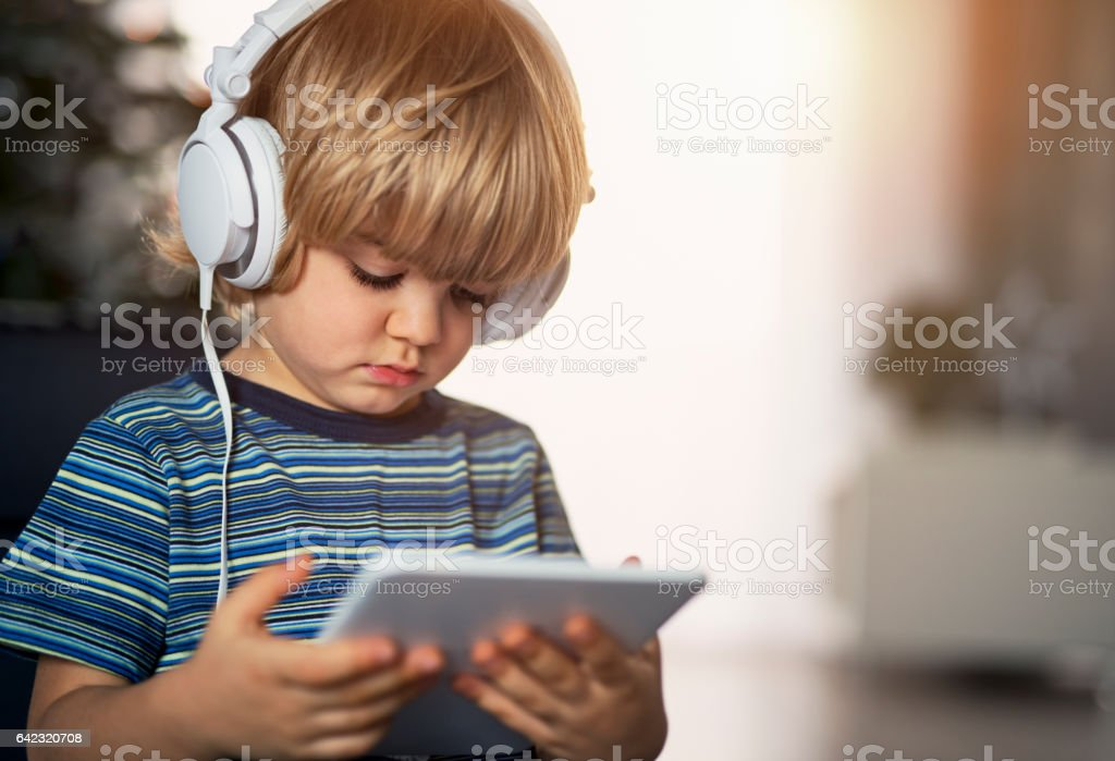 Cute little boy using digital tablet stock photo