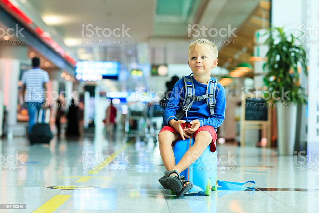 cute little boy waiting in the airport stock photo